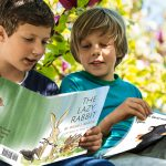 Two boys sitting ina tree reading The Lazy Rabbit and All in the Same Boat hardbacks