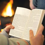 Woman in jeans and creen top reading a paperback copy of Razor in front of an open fire