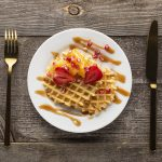 Plate with waffle, icecream and strawberries on wooden plank table and gold knife and fork